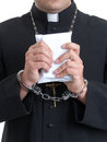 Priest with bribe catholic handcuffed holding envelope staffed money Stock Photography