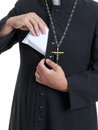 Priest with bribe catholic putting thick envelope staffed money into cassock Royalty Free Stock Images
