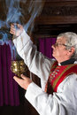 Priest with incense burner in red chasuble burning during mass Royalty Free Stock Photos