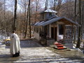 Priest prays the church in the woods crampotani valcele romania Stock Photos
