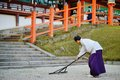 A priest rakes at kasuga taisha grand shrine november in nara jp founded in the shrine is a unesco world heritage site Royalty Free Stock Images