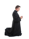 Priest with rosary catholic klneeling and saying his beads Royalty Free Stock Photography