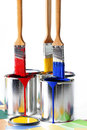Primary colors on paint brushes the of red yellow and blue over cans of containing the same color chips scattered Stock Photos