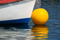 Primary colours red white and blue boat with a bright yellow buoy float reflected in blue waters Stock Images