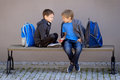 Primary education, school, friendship concept - two boys with backpacks sitting, talking and playing with spinner Royalty Free Stock Photo
