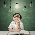 Primary school student sits under light bulb Royalty Free Stock Photo