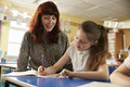 Primary school teacher helping with classwork at girl�s desk Royalty Free Stock Photo