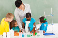 Primary science class teacher and students in with young girl using microscope Royalty Free Stock Photo