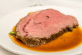 Prime rib in au jus a delicious slice of medium rare on a white plate with gravy or Royalty Free Stock Photography