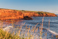 Prince edward island cliffs the rocky shore of at daybreak illuminating the and rocks bright red Stock Images