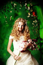 Princess girl lovely in a lush white dress stands under a floral arch over green background Stock Photography