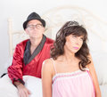Princess and playboy retro style pretty bored women with tiara on a white bed Royalty Free Stock Images