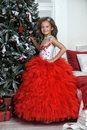 Princess in red and white dress standing near the Christmas tree