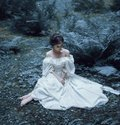 The princess sits on the ground in the forest, among the fern and moss. An unusual face. On the lady is a white vintage