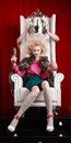 Princess woman in fur coat sitting on throne studio shot Royalty Free Stock Photo