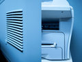 Printer fax scanner device in modern office and its lateral ventilation view blue technological mood color cast Royalty Free Stock Images