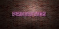 PRIORITIES - fluorescent Neon tube Sign on brickwork - Front view - 3D rendered royalty free stock picture