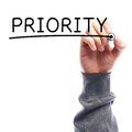 Priority hand with marker writing on transparent board against white background Royalty Free Stock Photos