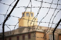 Prison barbed wire in front of the guard tower selective focus Stock Photos