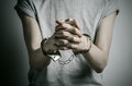 Prison and convicted topic: man with handcuffs on his hands in a gray T-shirt on a gray background in the studio, put handcuffs on Royalty Free Stock Photo
