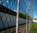 Prison security facilities barbed wire and brick walls in order to secure area Royalty Free Stock Image