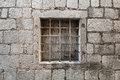 Prison wall with metal window bars locked ancient stone Stock Photo