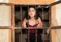 Prison woman young behind bars of a derelict building Royalty Free Stock Photography