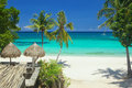 Private beach with hut to sahde from sun and white clean sand over bluish water Stock Photos