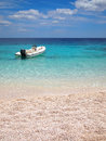 Private beach with speedboat in an emerald sea in front of a white sand on the east coast of sardinia italy Stock Photos