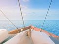 Private boat trip on open sea. Image shows legs of a woman lying on a thick and comfortable cushion laid on top of boat. Royalty Free Stock Photo