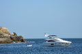 Private luxury yacht anchored near rocks in small bay with dingy Royalty Free Stock Photo