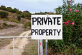 Private property sign on a metal gate on the dirt road Stock Photos