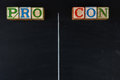Pro and con list childrens blocks spelling out on a chalk board with a chalk line to separate the columns horizontal format Royalty Free Stock Images