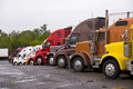 Procession colorful trucks on the truck stop after the rain cabins of multicolored semi lined up a with puddles pavement Stock Photos
