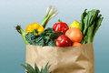 Produce in grocery bag assortment of fresh paper over gradient background Stock Photos