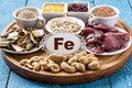 Products containing ferrum fe dried mushrooms bran buckwheat livers dogwood cashews oats lentils peanuts on a round cutting board Royalty Free Stock Photos