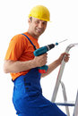 Profession builder with drill on stepladder Stock Images
