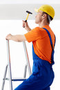 Profession builder on a ladder with hammer Stock Photo