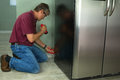 A professional appliance repair service technician man repairing