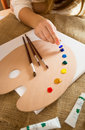 Professional artist squeezing oil paint from tubes on wooden pal Royalty Free Stock Photo