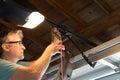 Professional automatic garage door opener repair service technician working closeup Royalty Free Stock Photo