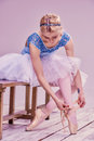 Professional ballerina putting on her ballet shoes. Royalty Free Stock Photo