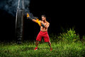 Professional boxer punching sandbag outdoors with his boxing glo Royalty Free Stock Photo