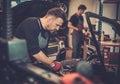 Professional car mechanic balancing car wheel on balancer in auto repair service. Royalty Free Stock Photo