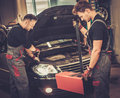 Professional car mechanics inspecting headlight lamp of automobile in auto repair service Royalty Free Stock Photo