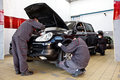 Professional car mechanics working in auto repair service stations.