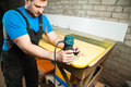 Professional carpenter processes the plastic edges of the countertop. The concept of furniture production Royalty Free Stock Photo