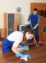 Professional cleaners in uniform cleaning room Stock Photos