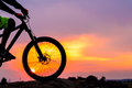 Professional Cyclist Resting with Down Hill Bike on the Rock at Sunset. Royalty Free Stock Photo