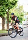 Professional cyclist riding bike on city streets Royalty Free Stock Photo